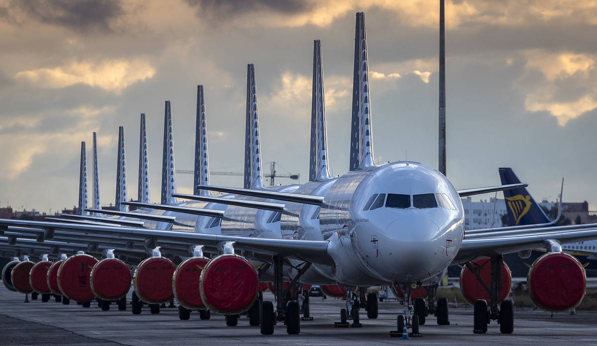 Vueling Airlines planes sit parked in a line at the Seville, Spain airport on Saturday, March 2 ...