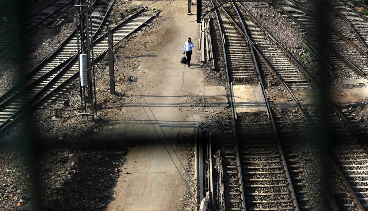 A passenger walks between railway tracks at New Delhi Railway station during a lockdown amid co ...