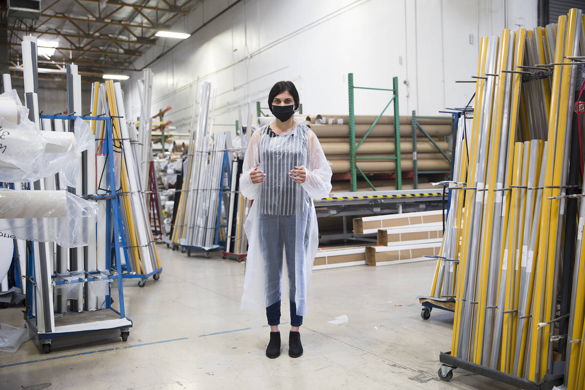 Employee Jordan Mevius wearing a gown and mask at Polar Shades in Las Vegas, Monday, March 23, ...