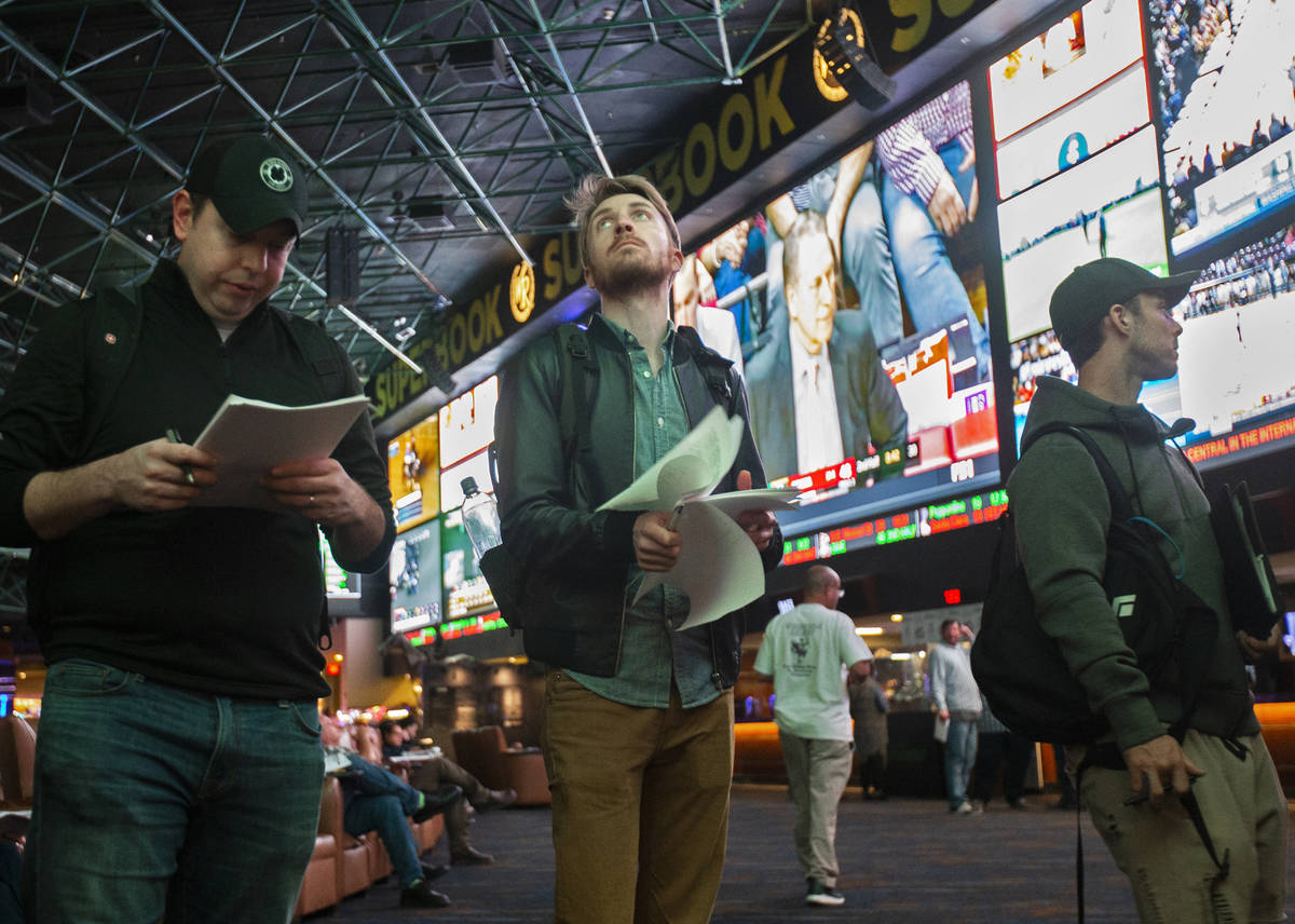 Rufus Peabody, middle, from Boston, Mass., waits in line at Westgate Sportsbook as Super Bowl p ...