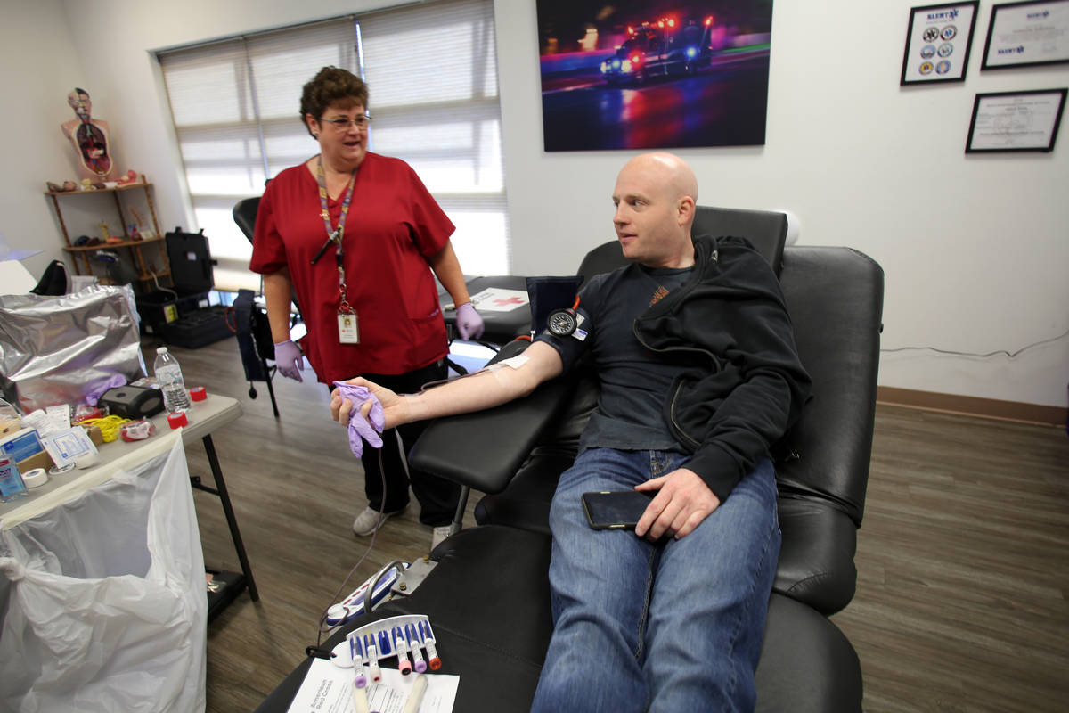 Phlebotomist Eva Clappa takes a blood donation from Matthew Daws during a blood drive sponsored ...