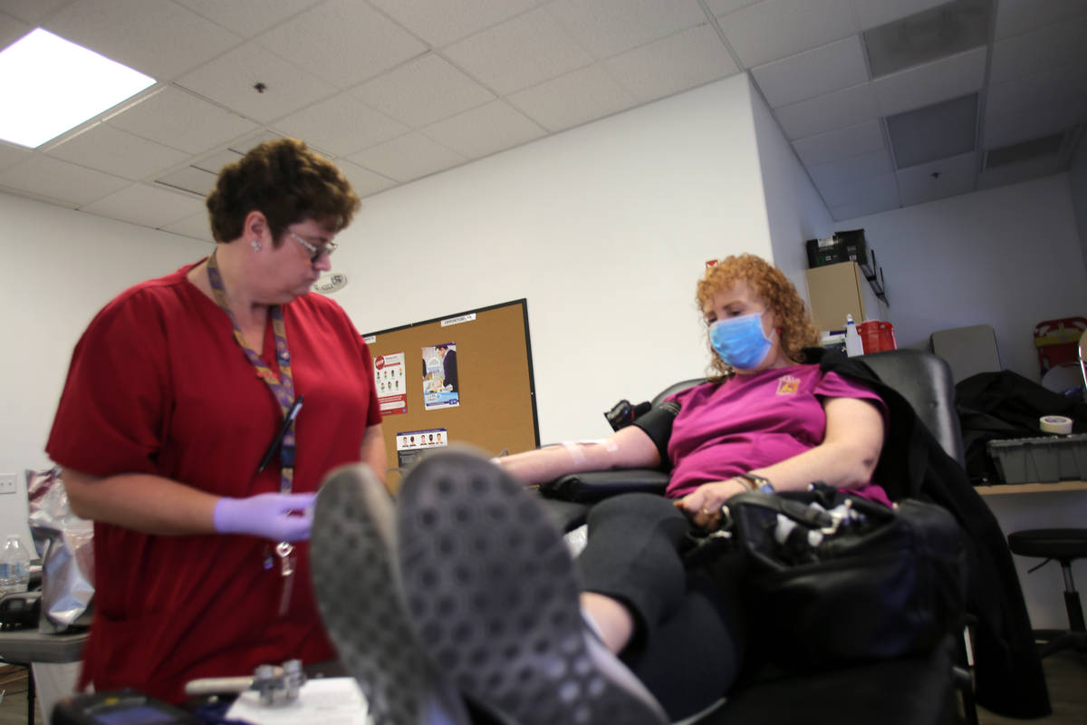 Phlebotomist Eva Clappa,. left, takes a blood donation from Susan Edwards during a blood drive ...