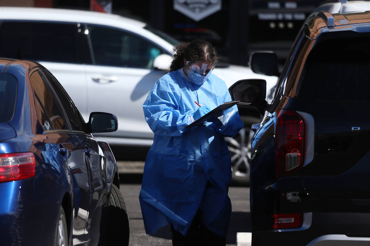 A lab technician assists people at the Sahara Urgent Care & Wellness center in Las Vegas, T ...
