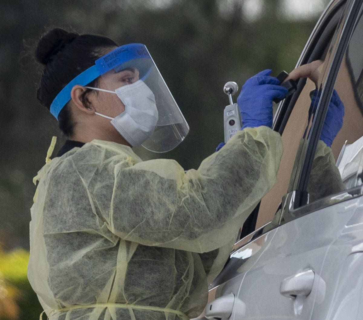 A UNLV medicine medical professional conducts a curbside test on a patient experiencing coronav ...