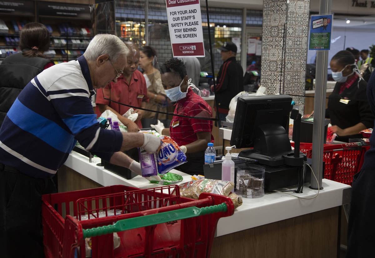 A screen divides a cashier, left, and customer right, at a pay point in a Spar supermarket, in ...
