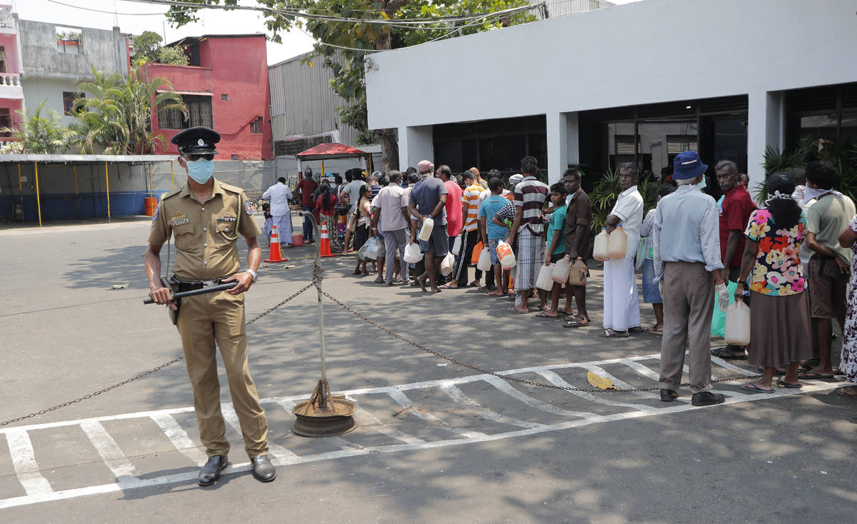 Sri Lankans queue for kerosene as a police officer stands guard during a temporary lift of a c ...