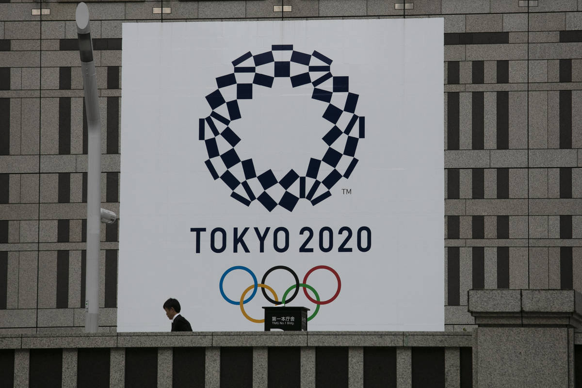 A man walks past a large banner promoting the Tokyo 2020 Olympics in Tokyo, Monday, March 23, 2 ...