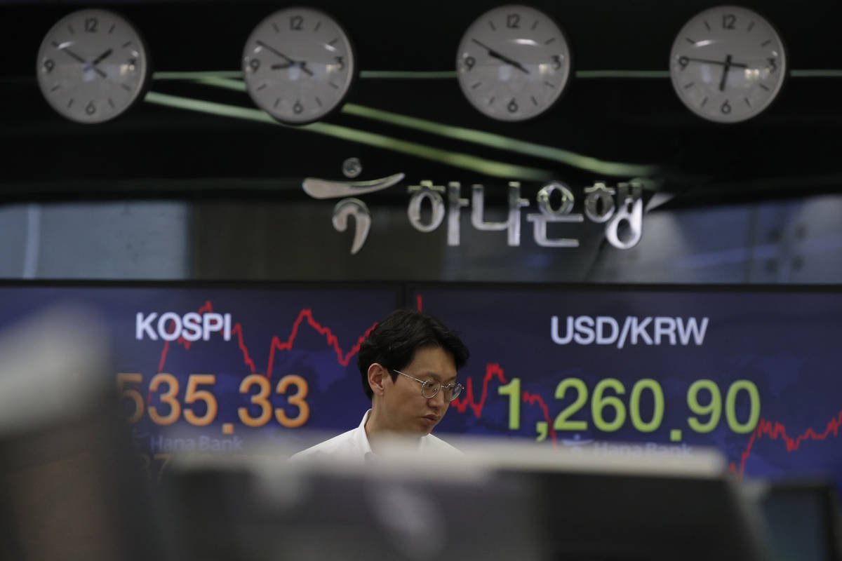 A currency trader walks by screens showing the Korea Composite Stock Price Index (KOSPI), left, ...