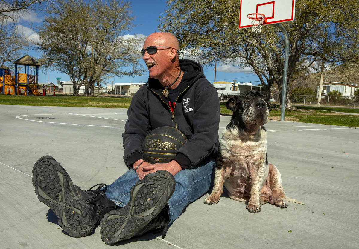 Searchlight resident Michael Howard takes a break from shooting some baskets with his dog Marth ...