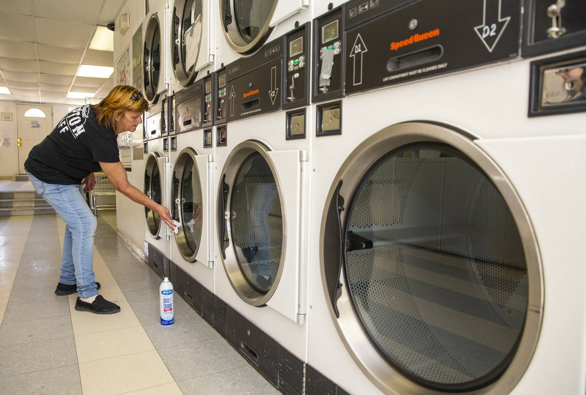 Bubbles 'n Bleach Laundromat manager Lynn Hess sanitizes each dryer on Tuesday, March 24, 2020 ...