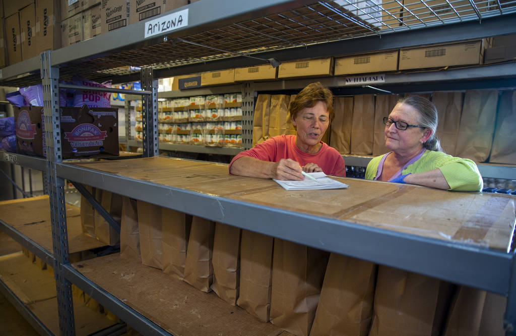 Pat Cartee, left, and Carol Rossi with the Colorado River Food Bank tally up their donation num ...