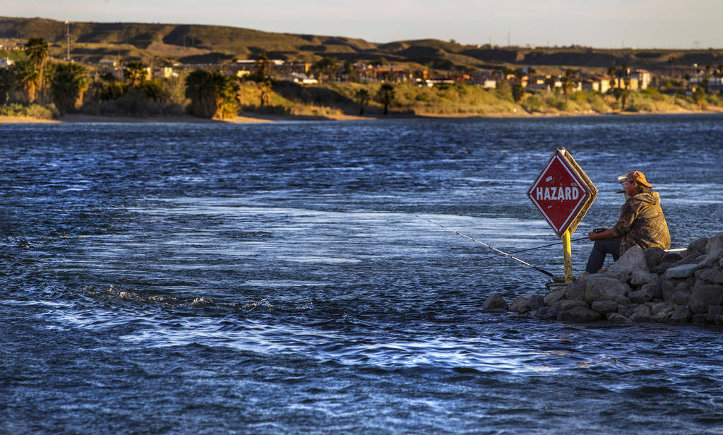 A man fishes in the Colorado River running beside Laughlin where the town is nearly shut down d ...