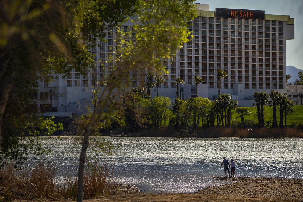 A couple stands beside the Colorado River running beside Laughlin where the town is nearly shut ...
