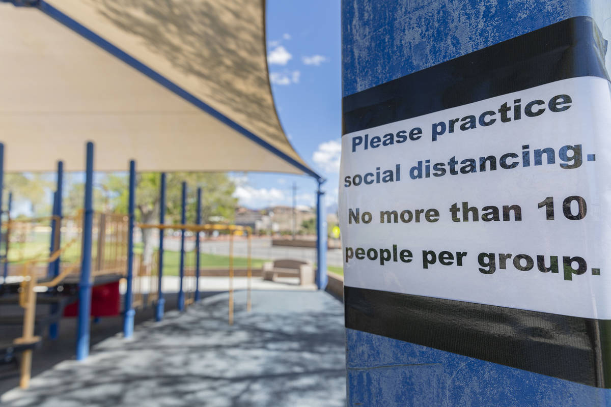 A sign asking for social distancing is seen at a playground in Veteran's Memorial Park in Mesqu ...