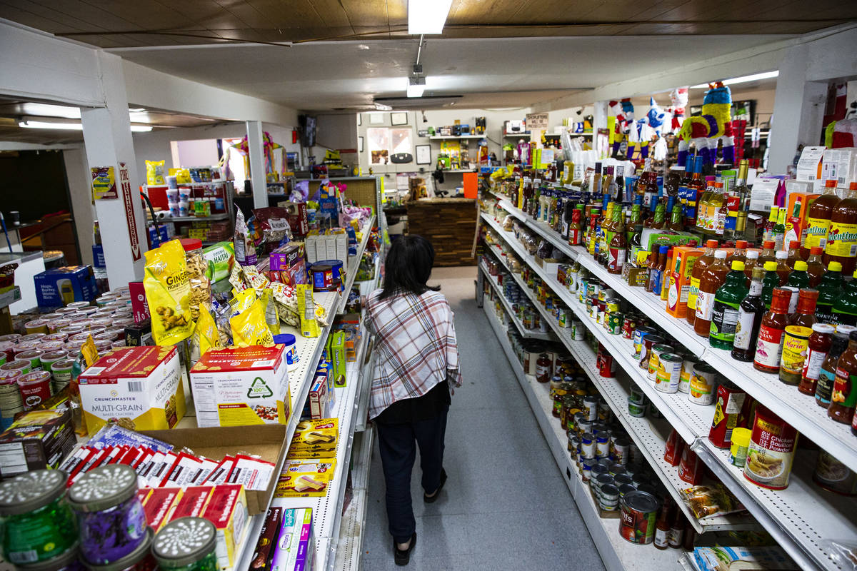 Sunny Martell, owner of Martell Market, walks through an aisle full of items stocked at the mar ...