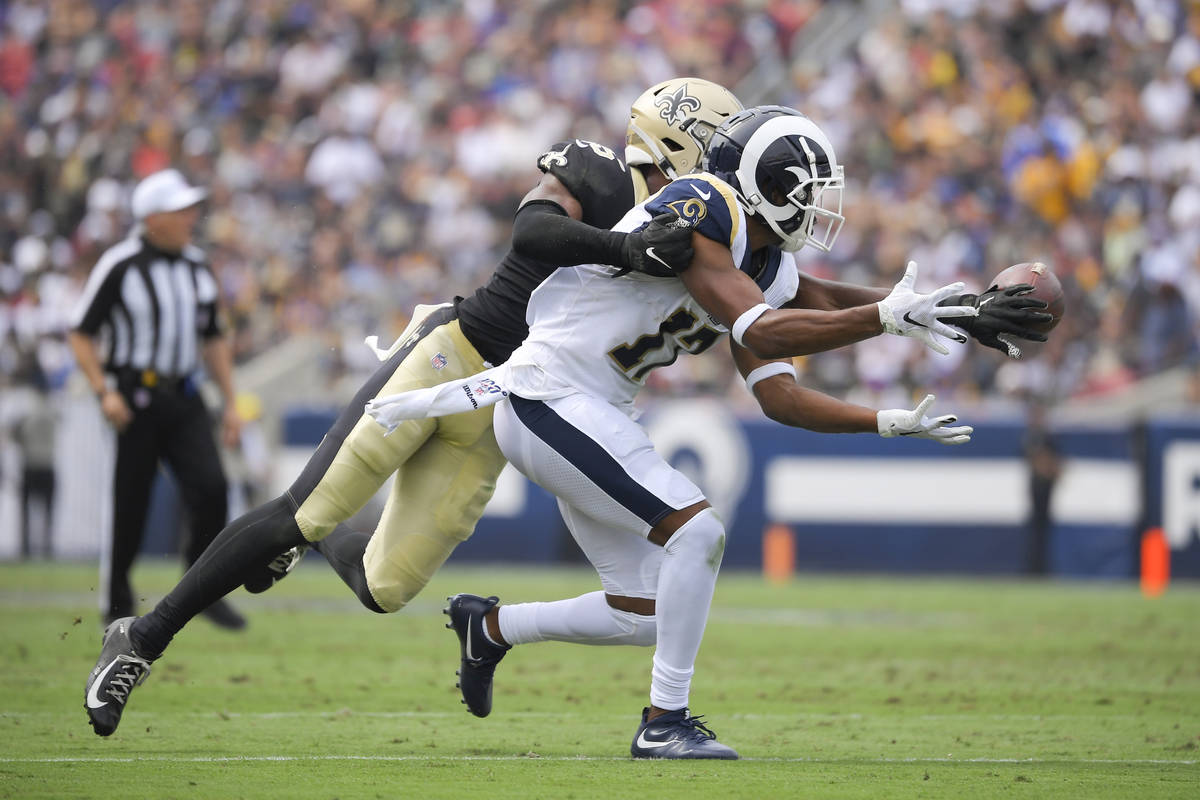 New Orleans Saints cornerback Eli Apple, left, breaks up a pass intended for Los Angeles Rams w ...