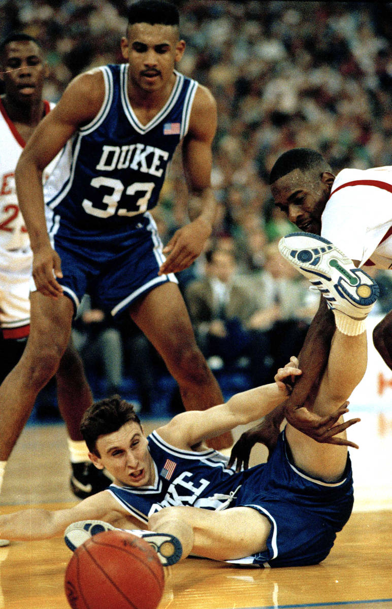 Duke's Bobby Hurley goes to the floor after the basketball as Stacey Augmon of UNLV, right, and ...