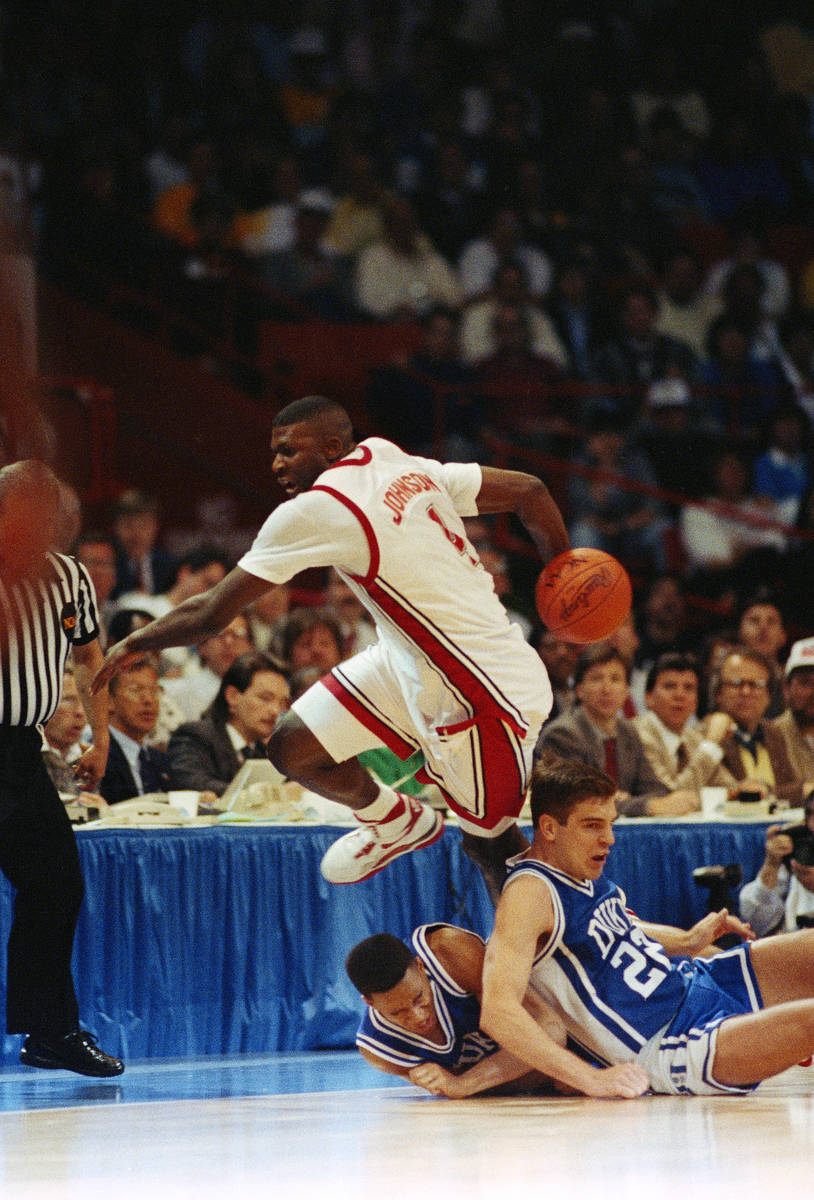 UNLV forward Larry Johnson keeps the ball in bounds behind his back while leaping over Duke pla ...