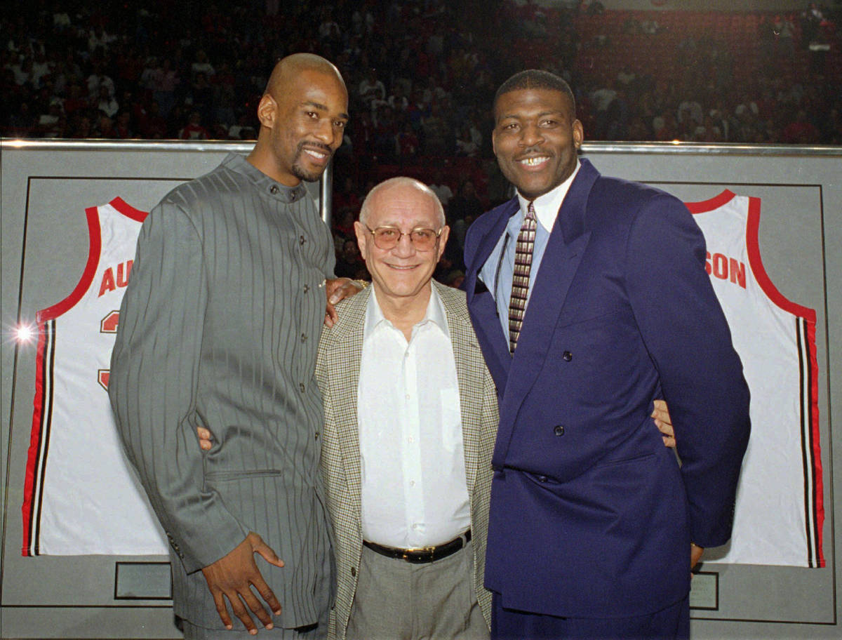 Former UNLV head basketball coach Jerry Tarkanian, center, poses with two of his former star pl ...