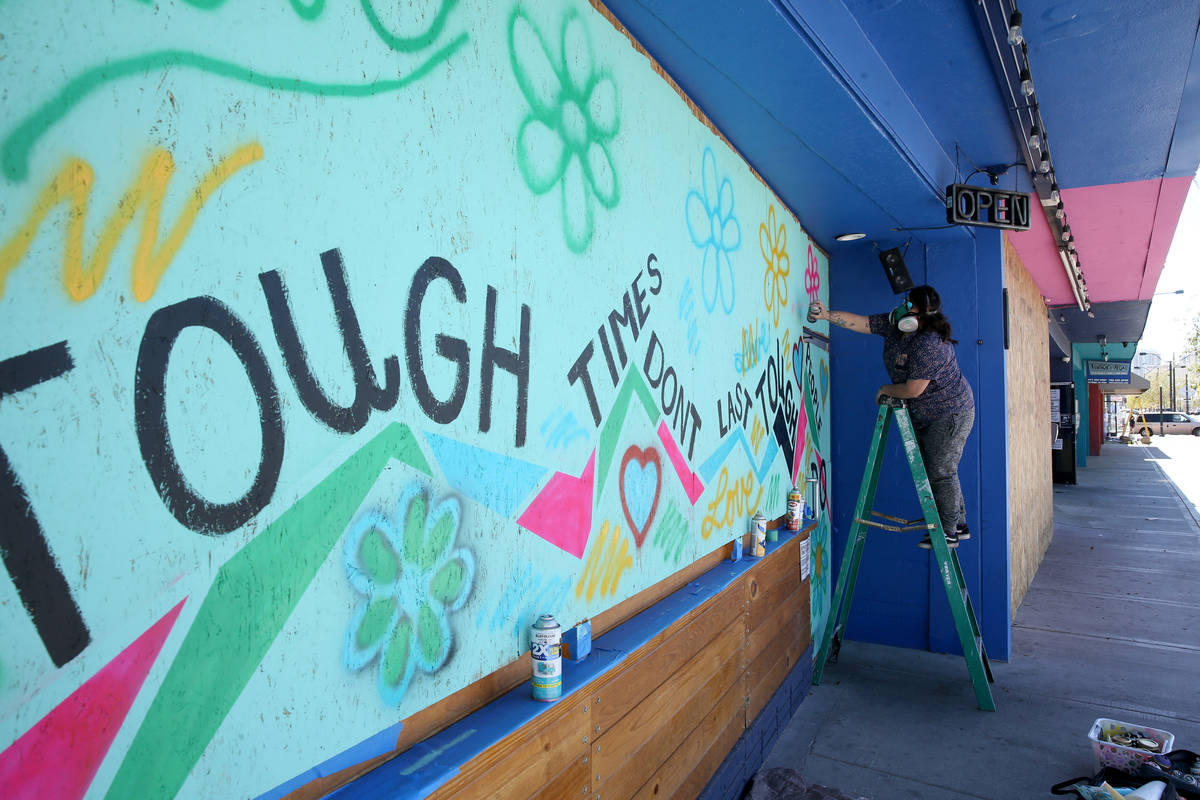 Artist Geneva Marquez paints a mural on the boarded up windows and door of Davy's @ReBar in the ...