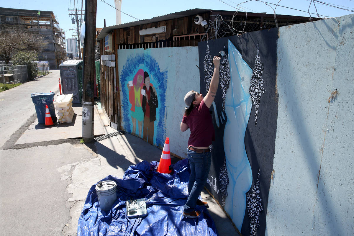 Artist R.J. Roberts paints a mural on the boarded up back door of ReBar in the Arts District in ...