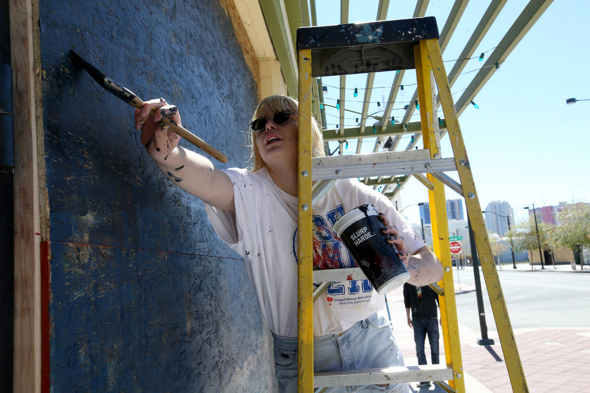 Artist Adelia Hoff paints a mural on the boarded up windows and door of Main Street Mercantile ...