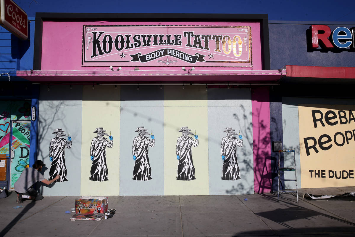 Artist Izaac Zevalking (aka: Recycled Propaganda) of Las Vegas paints a mural on the boarded up ...