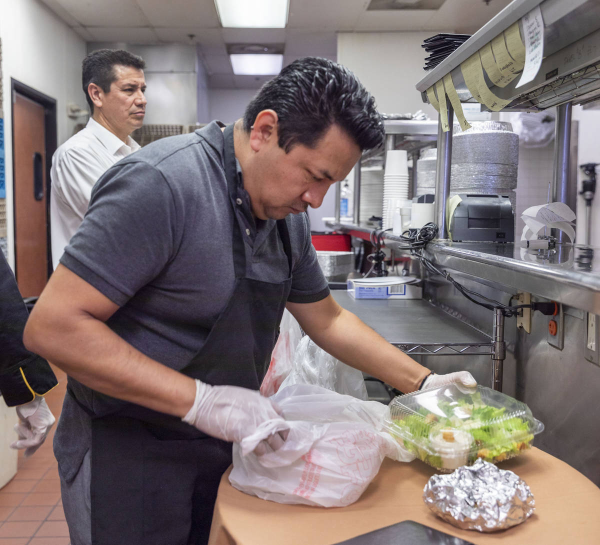 Gaetano's Ristorante waiter Juventino Angeles prepares a to-go order for curbside pickup at the ...