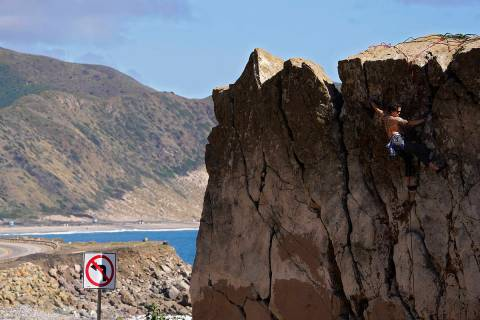 A climber climbs a rock formation along the Pacific Coast Highway, Monday, March 23, 2020, in M ...
