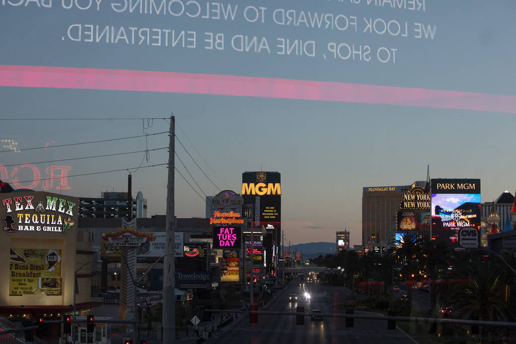 Lights turn on as the sun sets on the Strip on Tuesday, March 24, 2020, in Las Vegas. (Ellen Sc ...