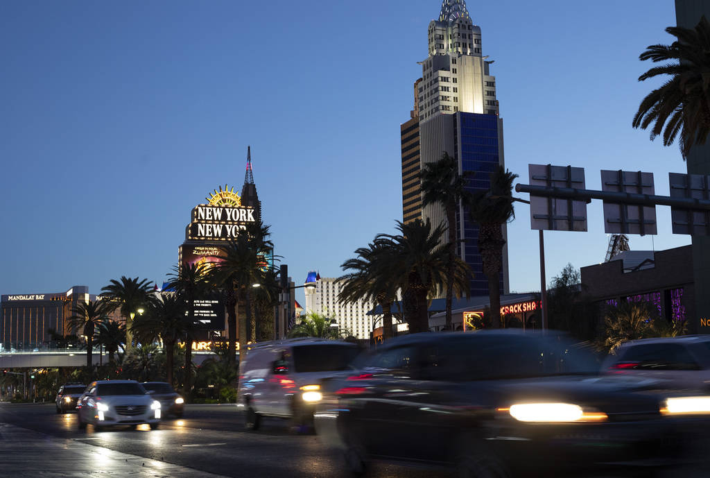 Vehicles pass down Las Vegas Boulevard as New York New York and Mandalay Bay shine in the backg ...