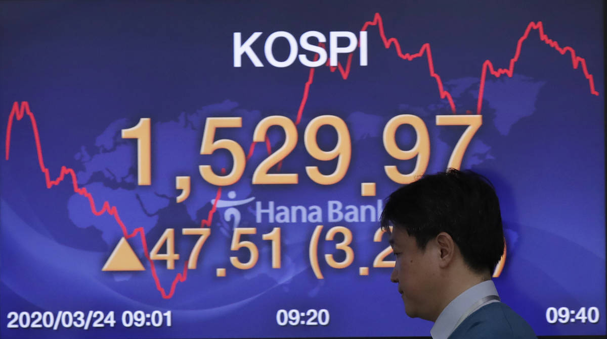 A currency trader walks by a screen showing the Korea Composite Stock Price Index (KOSPI) at th ...
