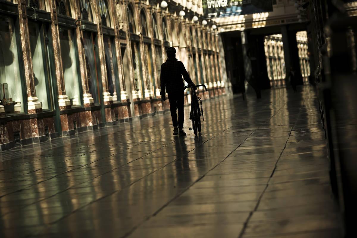 A man walks along along a virtually empty Royal Gallery of Saint Hubert commercial street durin ...
