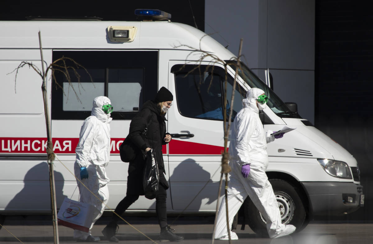 Medical workers escort a woman, suspected of having the coronavirus infection, to get out from ...