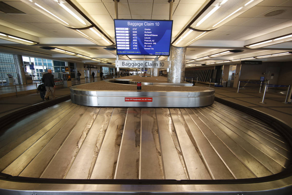 FILE - In this March 20, 2020 file photo, an empty baggage carousel spins in Denver Internation ...