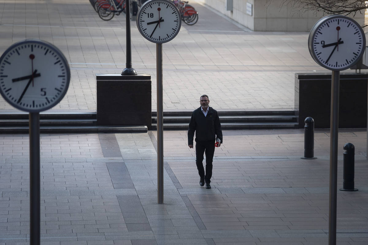 A woman walks in Canary Wharf, during rush hour, in London, Wednesday March 25, 2020. For most ...