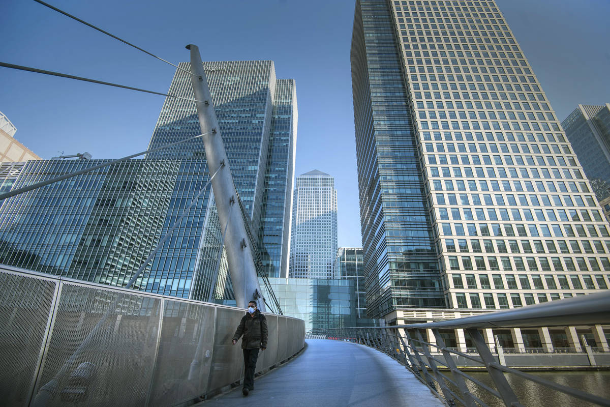 A man wearing a protective mask walks in Canary Wharf, during rush hour, in London, Wednesday M ...