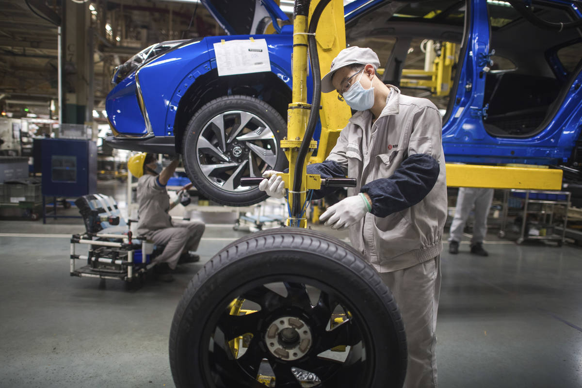 In this photo released by Xinhua News Agency, workers labor at an assembly line for Dongfeng Pa ...