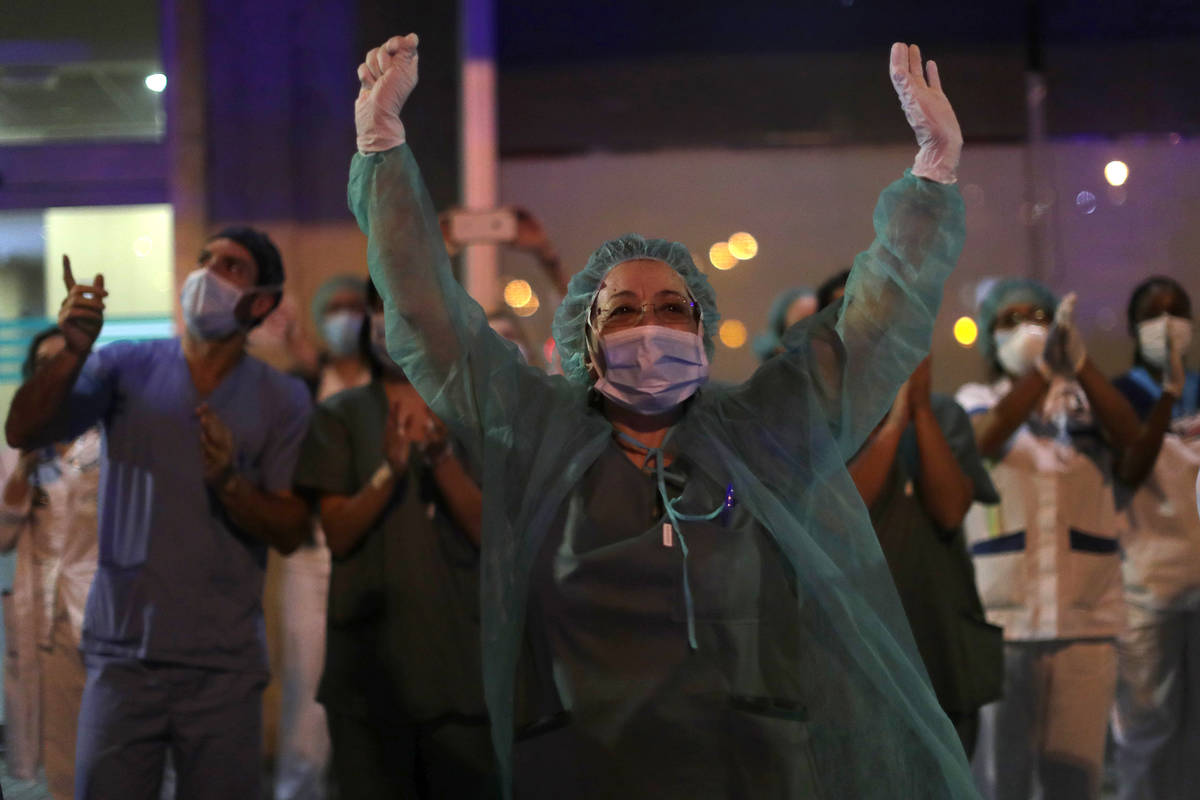 FILE, In this Saturday, March 21, 2020 file photo, health workers react as people applaud from ...