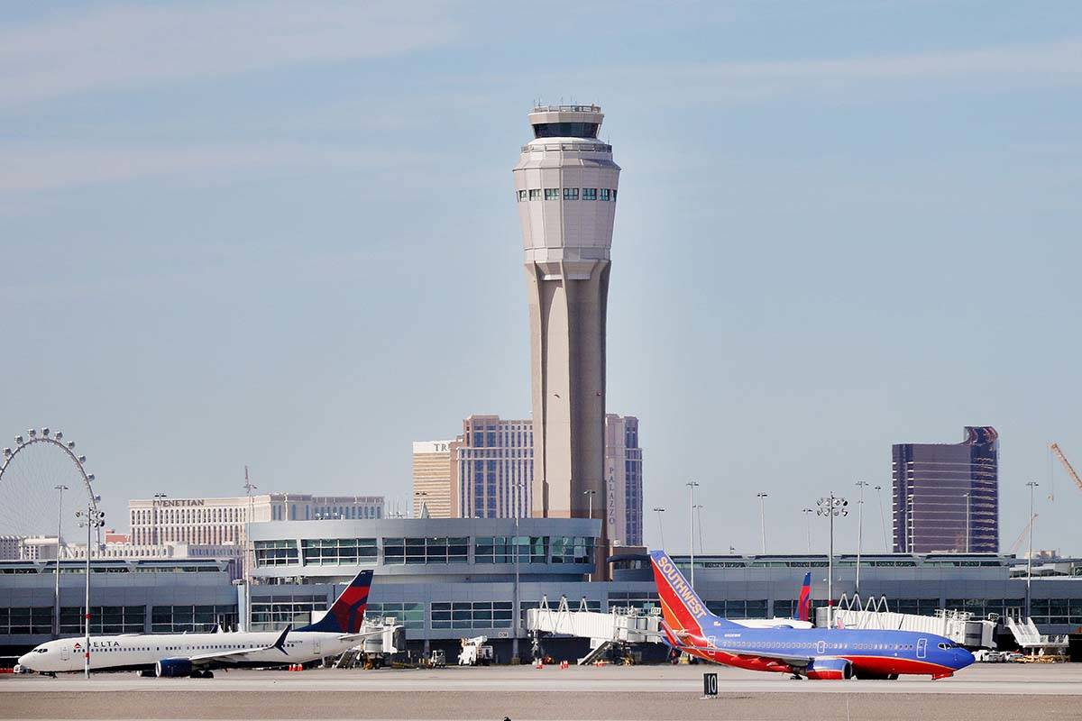 Planes both land and take off at the McCarran International Airport in Las Vegas on Thursday, F ...