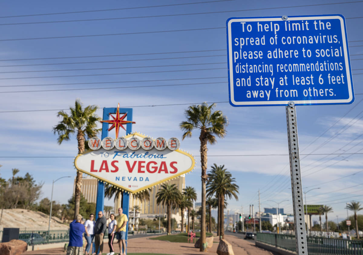 A sign is seen recommending social distancing as tourists from Sydney, Australia take photos un ...