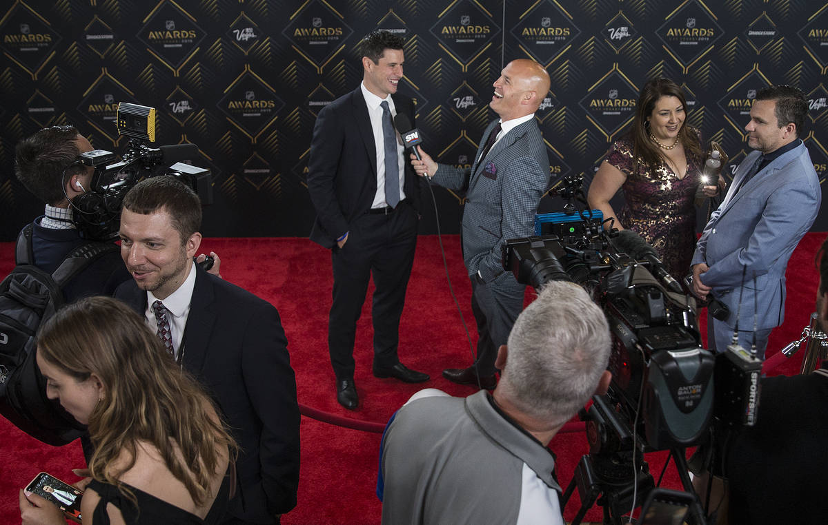 Pittsburgh Penguins center Sidney Crosby, top/middle, talks with media on the red carpet before ...