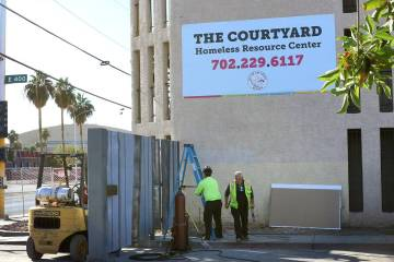 Workers install a gate at the corner of Las Vegas Boulevard and Foremaster Lane near the Courty ...