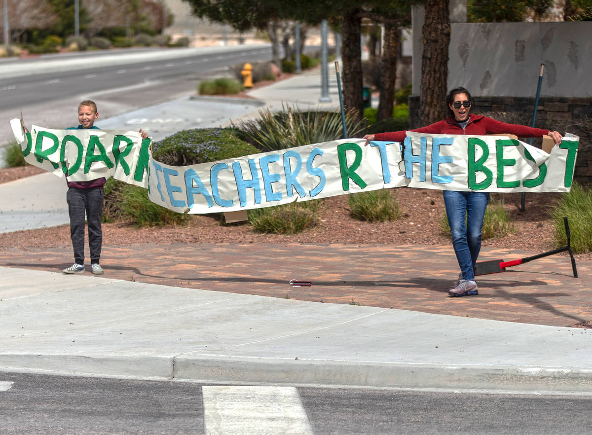 Las Vegas residents wave to teachers and staff from O'Roarke Elementary School who organ ...