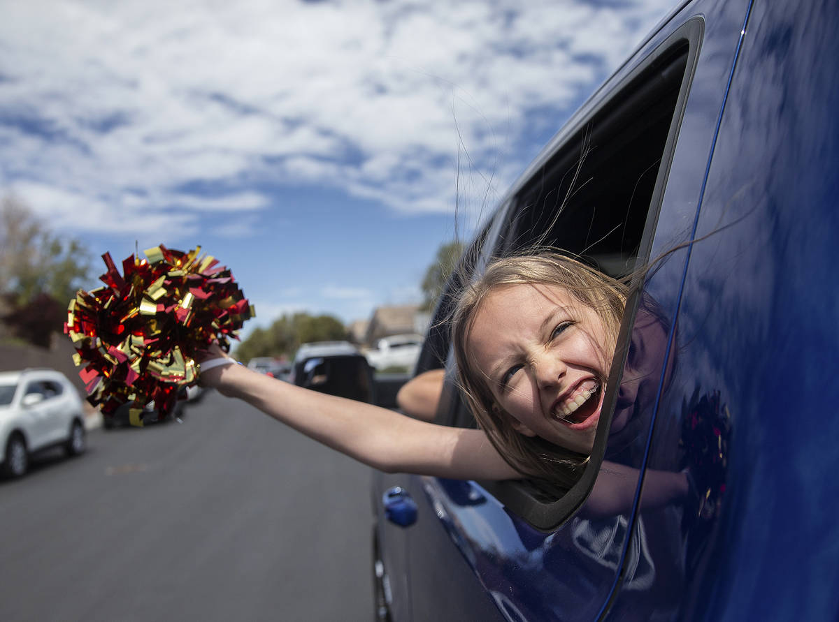 Ella Sproule, 11, waves from her mothers truck during a parade organized by O'Roarke Ele ...