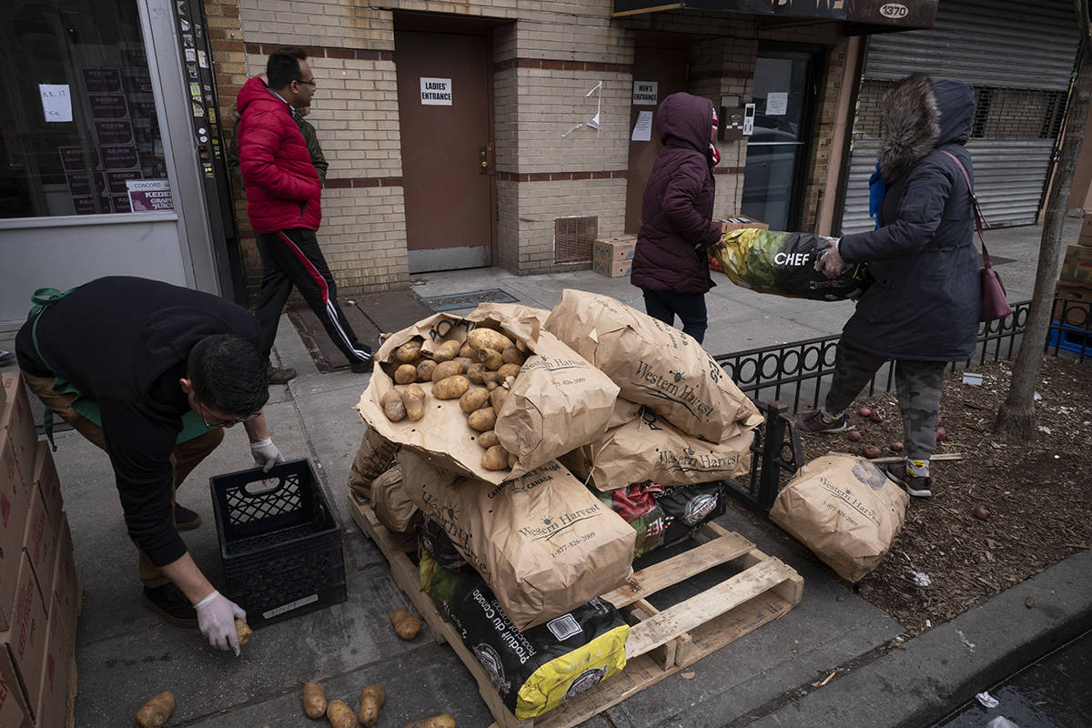 A manager at Masbia Soup Kitchen picks up spilled potatoes that are being distributed during th ...