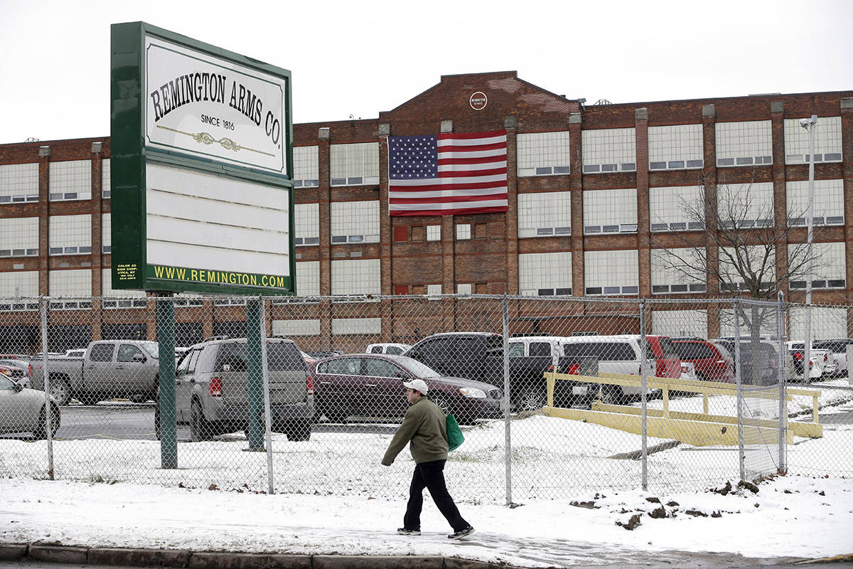 FILE - In this Jan. 17, 2013, file photo, a man walks past the Remington Arms Company in Ilion, ...