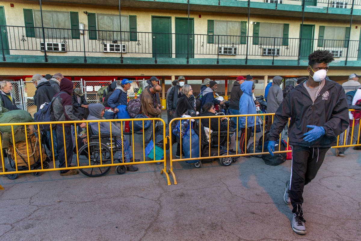 People line up at the Courtyard Homeless Resource Center to receive a sleeping mat for the nigh ...