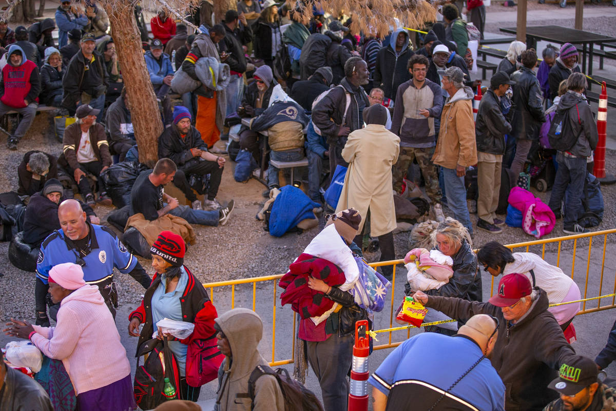 People receive a security check while in line at the Courtyard Homeless Resource Center to rece ...