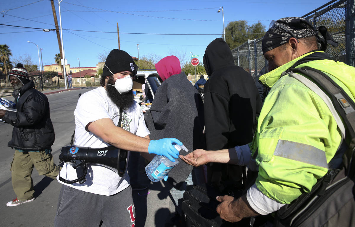 Joey Lankowski of homeless outreach organization Food Not Bombs squirts hand sanitizer for peop ...